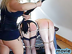 Cross-dressed man and his naked fellow slave get bent over a saw-horse, tied and lashed by a couple of kinky dommes